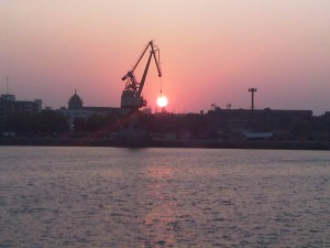 "Port crane working at Mumbai port-""Looks like Holding the Sun and dipping in Sea"""